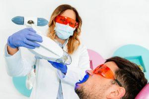 wybielanie zębów lampą na fotelu w gabinecie dentystycznym